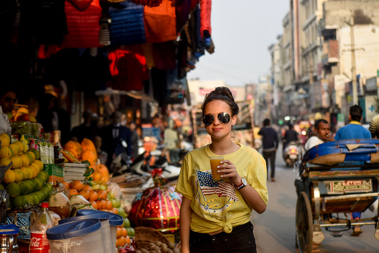 Street scene India, tourist girl drinking orange juice